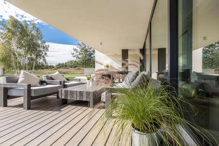 Szare meble ogrodowe na pokładzie podłogi na tarasie przestronnego mieszkania z widokiem na okolicę