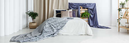 Dark blue accessories in spacious white bedroom with plants