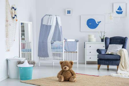 ストライプクッションとベージュの毛布は、子供のための寝室の白い木製のベビーベッドの隣にネイビーブルーのアームチェアに横たわっています
