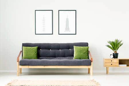 Plant en klok op houten kast naast een donkere bank met groene kussens in natuurlijke woonkamer interieur met posters