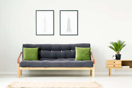 Plant and clock on wooden cupboard next to a dark settee with green cushions in natural living room interior with posters Foto de archivo