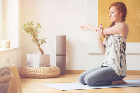 Happy woman sitting on her feet, on mat and stretching her arms and shoulders Stock Photo