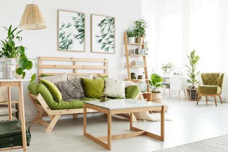 Houten groene bank met kussens tegen een muur met bladerenaffiches in het binnenland van de ecowoonkamer met installaties en houten lijst