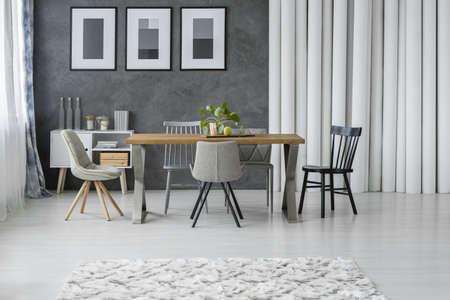 나무 테이블과의 자 및 찬장 및 종이 튜브 옆 회색 식당에서 패턴 카펫