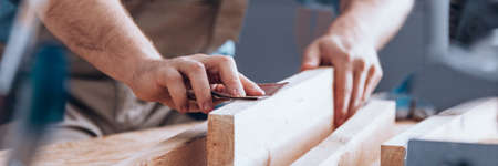 Close-up van houtbewerker die het houtoppervlak gladstrijkt met schuurpapier Stockfoto