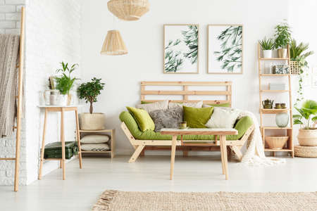 Table and plants on wooden shelf in floral living room interior with green sofa against a wall with leaves posters