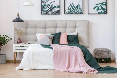 Pastelkleurlakens op bed met beige bedhead in het slaapkamerbinnenland van de vrouw met bladerenaffiches op de muur en vaas op wit nachtkastje