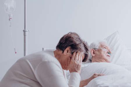 Droevige, oudere vrouw die haar zieke echtgenoot bekijkt die in bed in het ziekenhuis ligt Stockfoto