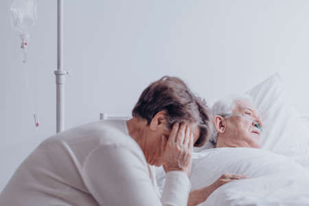 Sad, elder woman watching her ill husband lying in bed in hospital