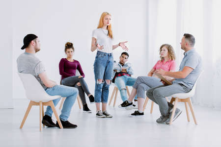 Problematic girl standing inside a circle during group therapy with rebellious teenagers Banco de Imagens - 93274809