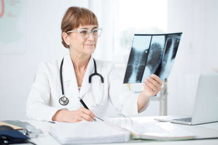 Pulmonologist with stethoscope looking at an X-ray picture of a cigarette smoker in an office with laptop Standard-Bild