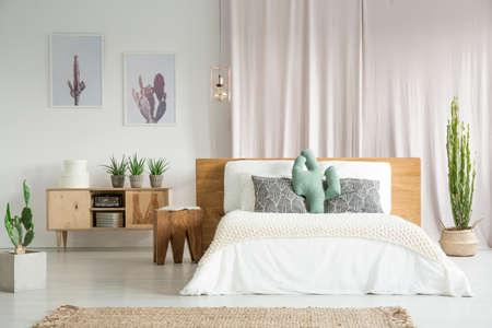 Cactussen overal in ruime slaapkamer met houten meubelset