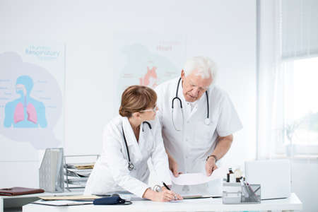 Cardiologists discussing patients case in hospitals office with poster and desk
