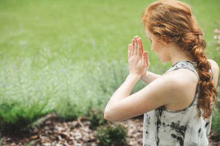 Focused red-haired woman with joined hands meditating in the garden Stock Photo
