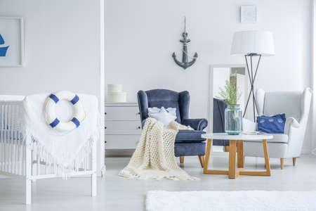 해양 스타일에 유아를위한 밝은 침실에 작은 테이블에 서있는 흰 꽃과 꽃병