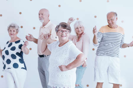 Happy grandmother dancing with smiling friends during New Year's Eve party Standard-Bild