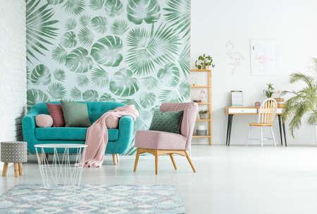 Open verwaardiging van modern appartement met turquoise bank in de woonkamer en werkruimte tegen witte muur Stockfoto