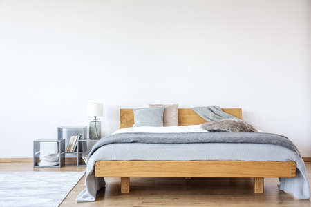 Grey pillow on wooden king-size bed in bright bedroom with copy space on the wall and lamp on a shelf