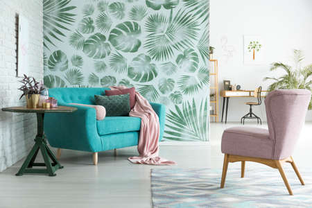 Pastel pink armchair standing in front of a blue couch with pink blanket in botanic interior of open living room