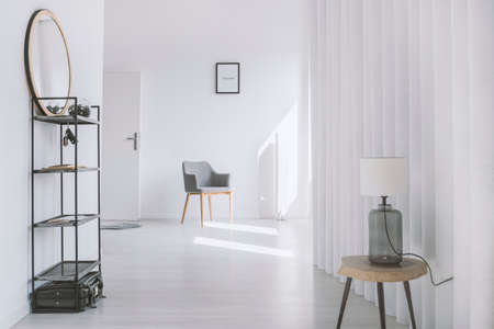 Mirror on industrial shelf and lamp on wooden stool in white corridor with grey chair next to door Stock Photo