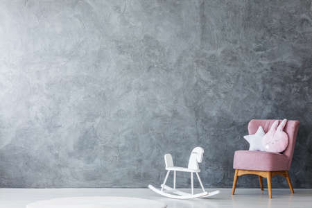 Pastel pillows on pink armchair next to white rocking horse against concrete wall with copy space in empty kids room interior