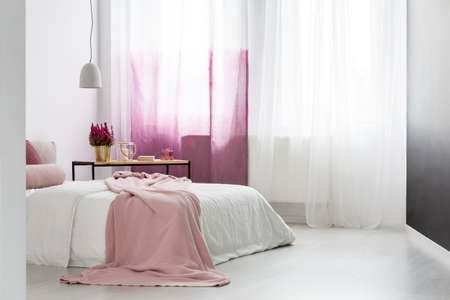 Bright bedroom with big window and pink blanket lying on a bed with white bedsheets