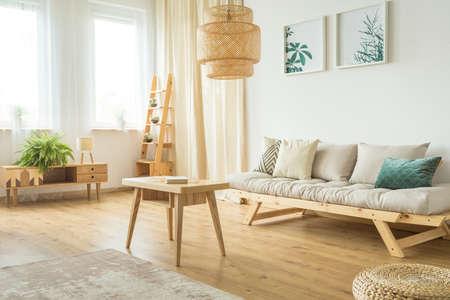 広々としたベージュと白いリビングルームのインテリアで木製のコーヒーテーブルの上にぶら下がる大きなランプ