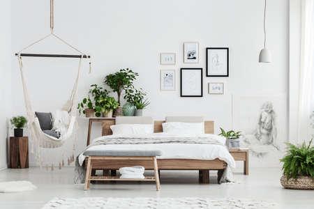 Hangmat met dekens in de buurt van planten op houten kruk en bed met witte beddengoed in natuurlijke slaapkamer interieur met posters Stockfoto