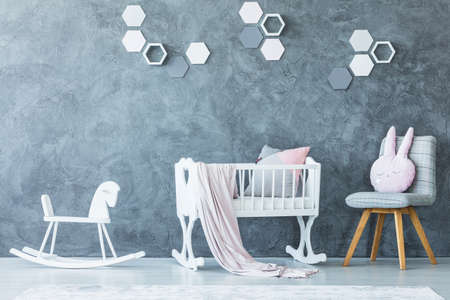White cradle with blanket between rocking horse and chair with pillow in child's bedroom interior with honeycombs on concrete wall