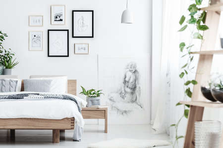 Drawing on white wall of simple bedroom interior with plant on wooden nightstand next to a bed with pillows