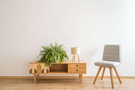 小さなランプとシダが付いている木製の食器棚の隣に立ち往生するシンプルな灰色の椅子