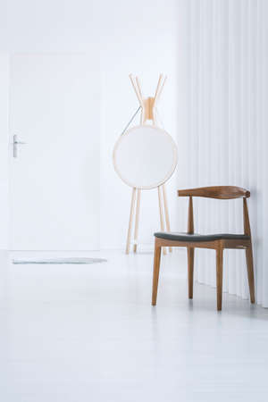 Dark wooden chair in white empty anteroom with mirror on hanger