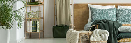 Green leather suitcase standing next to bed with wooden bedhead and floral cushions in white bedroom interior Imagens