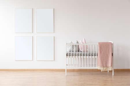 유아를 위해 설계된 간단하고 밝은 방에서 분홍색 담요 및 포스터 모형이있는 흰색 침대