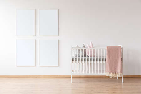 White crib with pink blanket and poster mockups in simple, bright room designed for a toddler