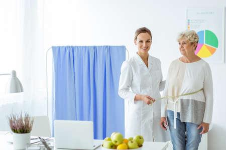 Lächelnder messender Patient des Ernährungswissenschaftlers auf Diät im Büro, zum des Fortschritts zu überprüfen