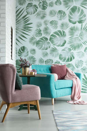 Close-up of elegant living room interior with turquoise sofa and pastel pink armchair next to white brick wall
