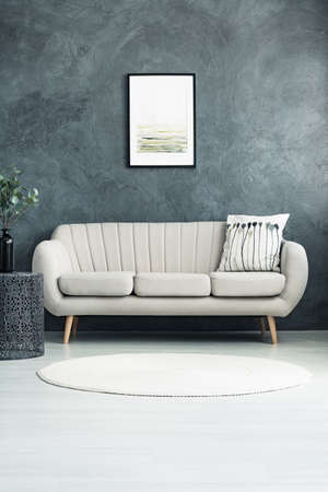 Pillow on beige sofa against concrete wall with poster in living room with white carpet and vase on table