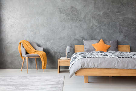 Orange star pillow on wooden bed against concrete wall with copy space in grey bedroom with chair