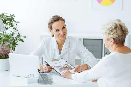 Lächelnder Diätetiker, der einen Diätplan während der Beratung mit Patienten im Büro mit Laptop auf Schreibtisch hält Standard-Bild