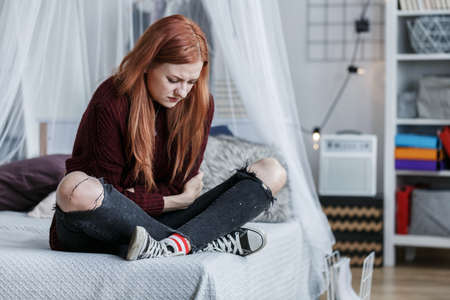 Red-haired, young girl sitting on her bed with stomach pain