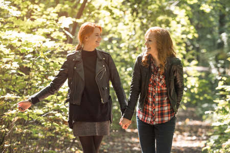 Laughing girls couple holding hands during a walk in a sunny park