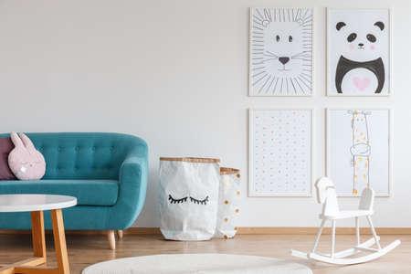 Scandi design do quarto garoto brilhante com cavalo de balanço branco, sofá azul e cartazes com animais