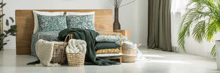 Knot pillow in a basket standing in front of a green bed with wooden bedhead and floral bedsheets