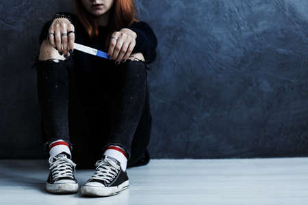 コピースペースを持つ壁に対して床に座っているティーンエイジャーのクローズアップ,妊娠検査を開催