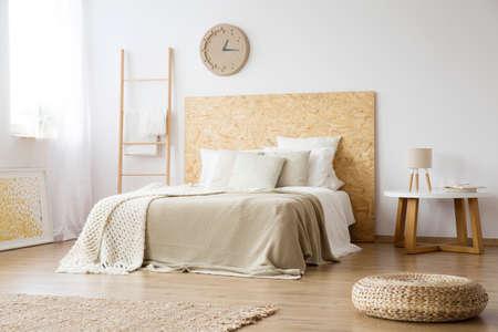 Poef, tapijt en ladder in natuurlijke slaapkamer met bruine deken op bed tegen witte muur met klok