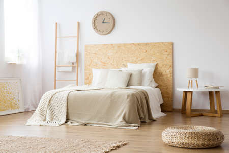 Pouf, rug and ladder in natural bedroom with brown blanket on bed against white wall with clock