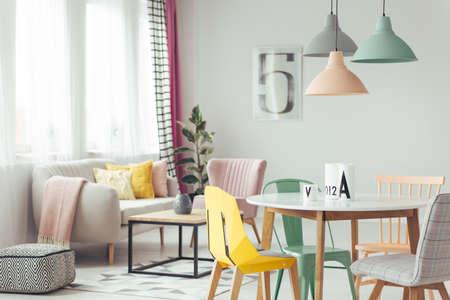 Pastel lamps above wooden round table in bright living room interior with patterned pouf and yellow cushion on a sofa Reklamní fotografie - 93532928