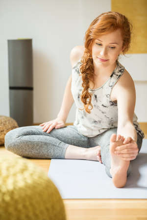 Young woman with a ponytail stretching on the floor during yoga class Stockfoto