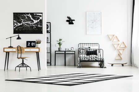 Monochromatic bedroom design for a teenager with metal bed and study space with laptop Banque d'images